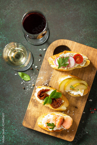 Antipasti snacks set for Wine. Variety Brushetta with Soft Cheese, Pear, Radish, Salmon and Dried Tomatoes served on a rustic wooden board on a stone table.