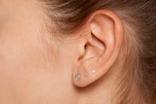 Closeup Of Female Ear With Three Earrings