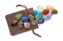 Crystal Healer's Precious Pouch Of Colourful Stones - A Selection Of 16 Different Crystal Healing Tumbled Stones Laid On A Brown Gift Pouch Isolated On A White Background