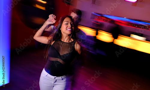 Pareja joven bailando salsa y bachata en una fiesta en club nocturno Tablou Canvas