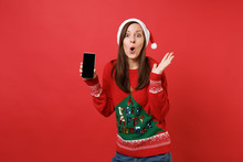 Amazed Santa Girl Looking Surprised Spreading Hands, Holding Mobile Phone With Blank Empty Screen Isolated On Red Background. Happy New Year 2019 Celebration Holiday Party Concept. Mock Up Copy Space.