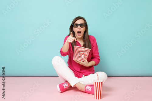 Full length portrait fun woman in rose shirt, white pants sitting on floor watching movie film isolated on bright pink blue pastel wall background studio фототапет