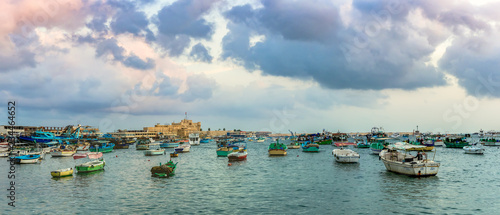 ALEXANDRIA, EGYPT - NOVEMBER 20, 2016: Cityscape with egyptian fisher boats, vessels and ships in the seaport at sunrise Wallpaper Mural