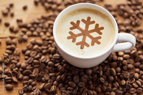 winter holidays and hot drinks concept - close up coffee cup with snowflake stencil picture and roasted beans on wooden table