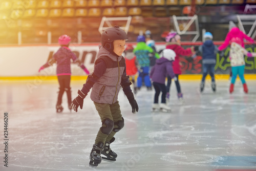 Tablou Canvas Adorable little boy in winter clothes with protections skating on ice rink