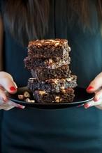 A Woman Holding A Plate Of Gluten-free Hazelnut Brownies
