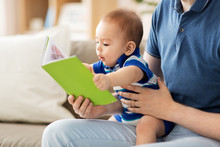 Family, Parenthood And People Concept - Happy Asian Baby Boy And Father With Book At Home