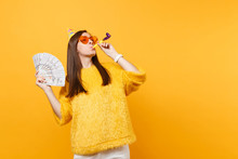 Cheerful Young Woman In Orange Heart Glasses, Birthday Hat With Playing Pipe Holding Bundle Lots Of Dollars Cash Money, Celebrating Isolated On Yellow Background. People Sincere Emotions, Lifestyle.