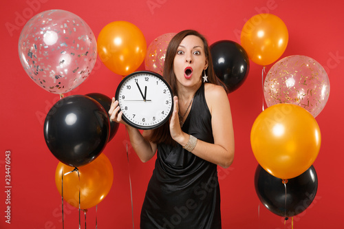 Photo  Shocked young woman in black dress celebrating holding round clock on red background air balloon