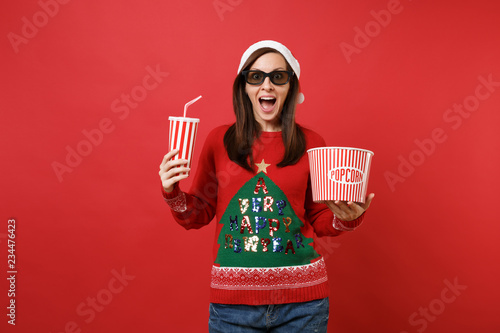 Платно Excited young Santa girl in 3d imax glasses watching movie film holding popcorn, cup of soda isolated on red wall background