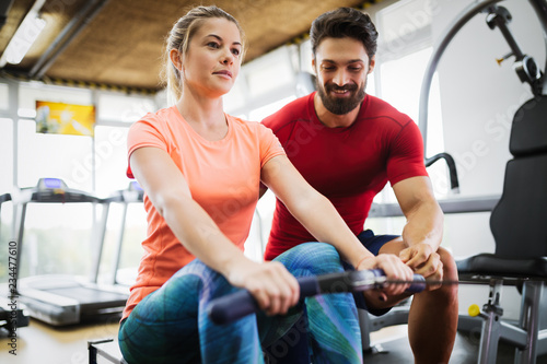 Young beautiful woman doing exercises with personal trainer - 234477610