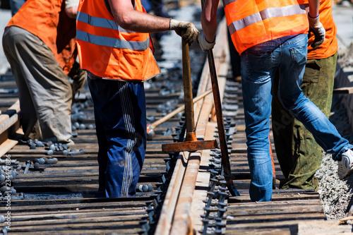 Fotomural Workers in bright uniforms lay railway or tram tracks