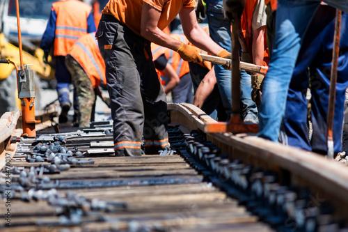 Cuadros en Lienzo Workers in bright uniforms lay railway or tram tracks