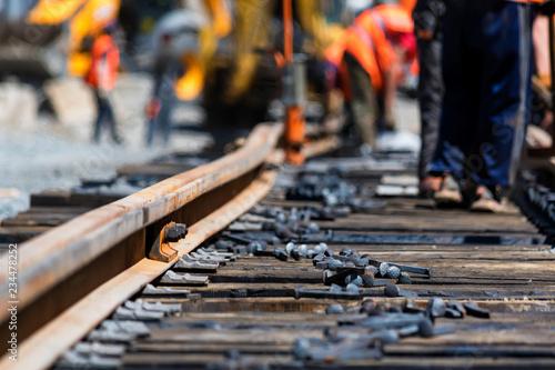 Fotografía Workers in bright uniforms lay railway or tram tracks