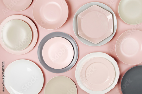 Plates and dishes for serving a festive table on pastel colors background Wallpaper Mural