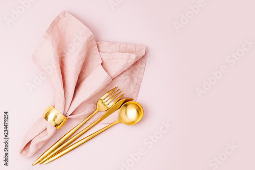 Gold cutlery and pale pink napkin  on pastel background Canvas Print