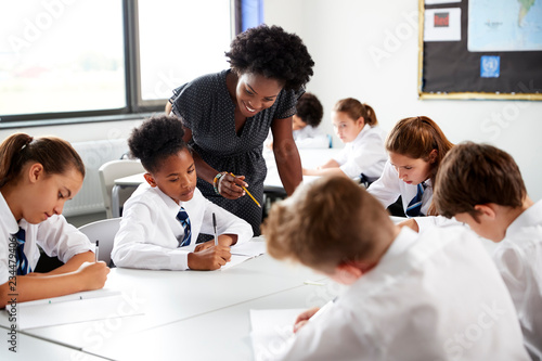 Foto Female High School Tutor Helping Students Wearing Uniform Seated Around Tables I