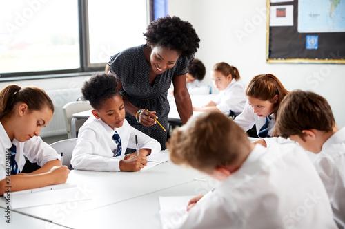Obraz na plátne Female High School Tutor Helping Students Wearing Uniform Seated Around Tables I