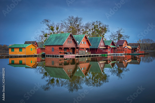 Fotografiet Tata, Hungary - Wooden fishing cottages on a small island at lake Derito (Derito