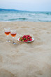 two glasses of wine and a plate of strawberries on a sandy beach, a picnic near the sea.