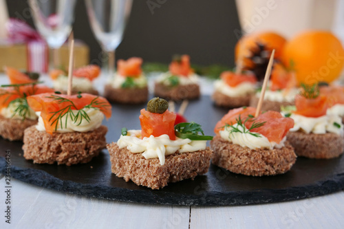 Smoked salmon canapes with cheese cream and capers on rye bread