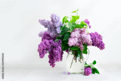 Fresh lilac flowers in glass vase over white table background