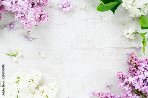 Fresh lilac flowers frame over white wooden background with copy space, flat lay top view floral composition