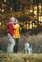 A Senior Couple With A Dog Sta...