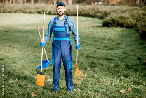 Slika na platnu Portrait of a professional male sweeper in blue uniform with sweeping tools in t