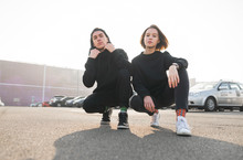 Young Couple Of Guys And Girls In A Stylish Casual Dress Are Sitting On The Street And Posing On The Camera. Fashionable Couple In Black Hoodie. Lookbook. Street Fashion Portrait