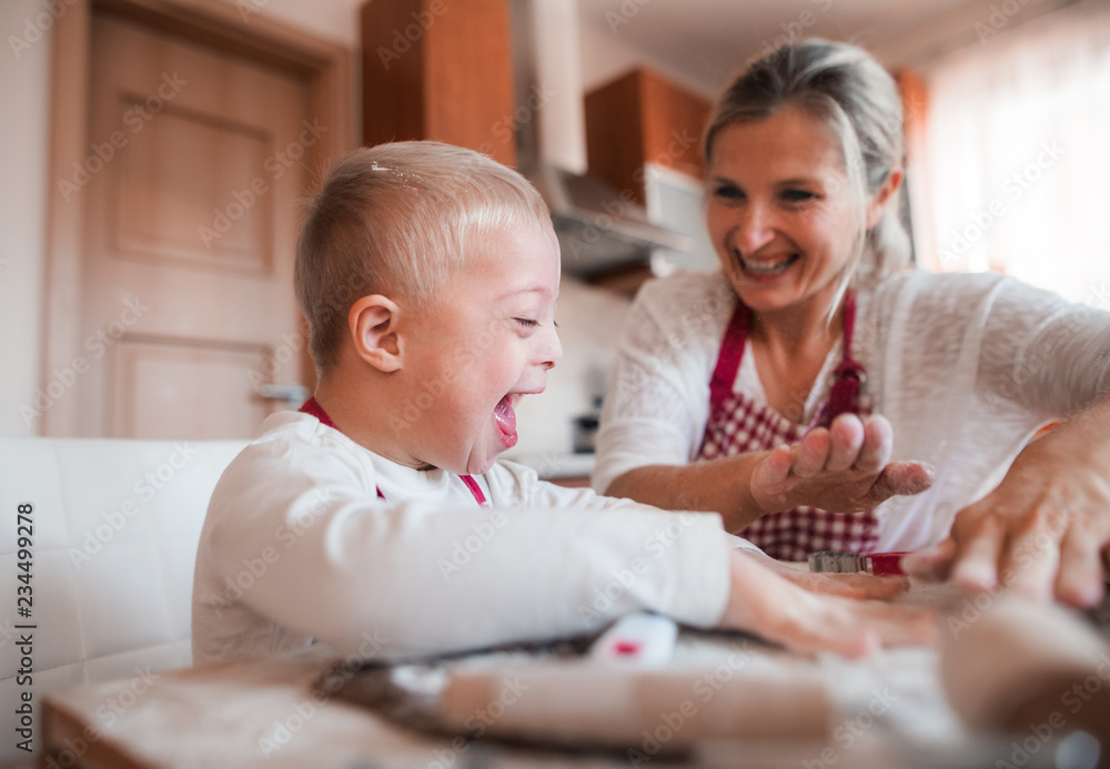 Fototapeta A laughing handicapped down syndrome child with his mother indoors baking.