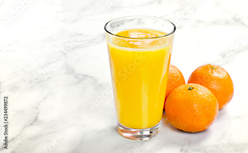 Fresh orange juice in a drinking glass, top view. Healthy fruit juice on white marble or stone background.