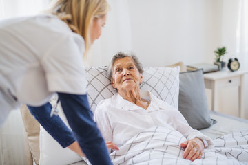 A health visitor talking to a sick senior woman lying in bed at home.
