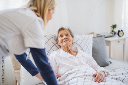 Fotografia  A health visitor talking to a sick senior woman lying in bed at home