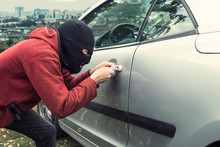 Close Up Of Man In Black Robber Mask Breaking The Car Lock On A City Background. Ill-intended Thief Forces The Vehicle Lock With A Picklock. Evil-doer Encroaches A Parked Automobile. Criminal Attempt