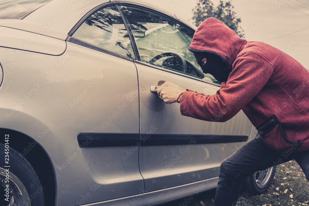 Fototapeta Side view of car being forced by a man in hoodie and mask. Thief tries to steal vehicle from a parking. Young male acts alone breaking the car door. Unknown person picklocks the automobile. Car fraud.