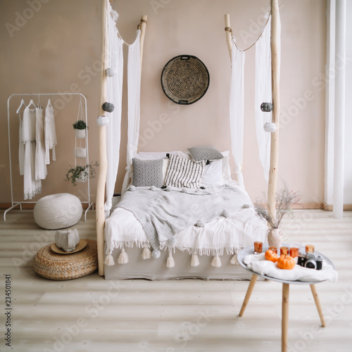 Papiers peints Style Boho Modern home interior design. Bed with wooden canopy and pillows, blanket and a bedside table with candles. Exotic bedroom interior, scandinavian style