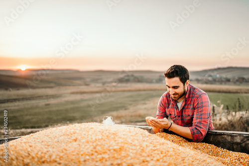 Portrait of harvester at sunset enjoying his harvest in tractor trailer Canvas Print