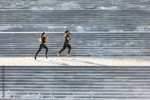 Couple of athletes do exercises for legs and fat burning on the big steps of the stadium on a sunny summer day. Concept of joint training and preparation for competitions. Copyspace