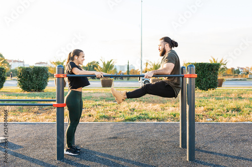Fotografía  Cute mixed race young girl and a strong athletic guy in good physical shape are engaged on uneven bars on the sports field on a sunny summer day
