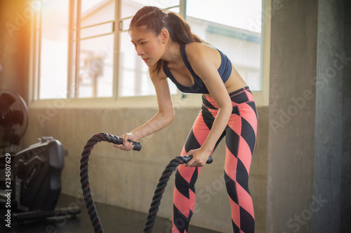 Fotografía  Woman training with battle rope in cross fit gym