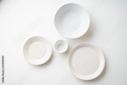 Leinwand Poster Porcelain plates of various form and size on white background