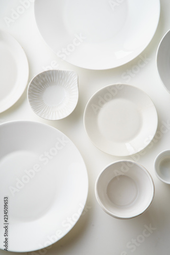 Fotomural  Porcelain plates of various form and size on white background