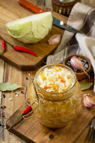 Sauerkraut variety preserving jars. Homemade Sauerkraut with Carrot on a wooden table. Fermented food.