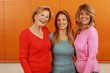 canvas print picture - Three middle age  girlfriends together in front of an orange Wall