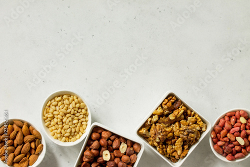 In de dag Buffet, Bar Various nuts in a ceramic bowl (walnut, almonds, pine nuts, hazelnuts) on a light stone table. The concept of a healthy dessert.Top view flat lay background. Copy space.