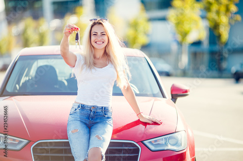 Photo of happy blonde with keys standing near red car Canvas Print