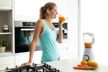 Beautiful Sporty Young Woman Looking Sideways And Drinking Vegetable Detox Juice While Listening Music In The Kitchen.