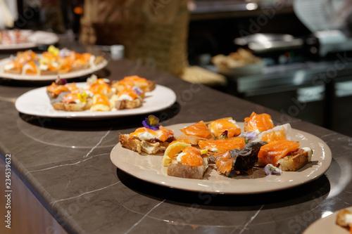 Photo sur Aluminium Entree Salmon tapas on open kitchen counter, hard light