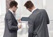 two businessmen reading a message on a digital tablet